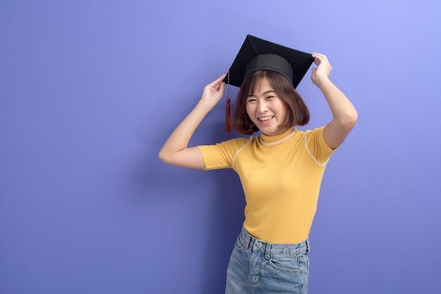 Um retrato de um jovem estudante asiático com chapéu de formatura sobre o fundo do estúdio.