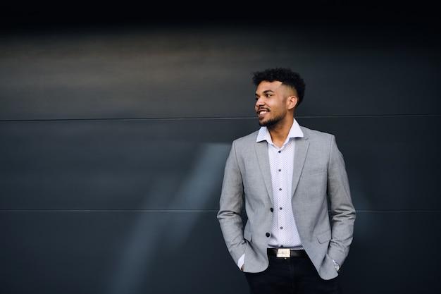 Um retrato de um jovem estudante em pé ao ar livre na cidade contra um fundo preto