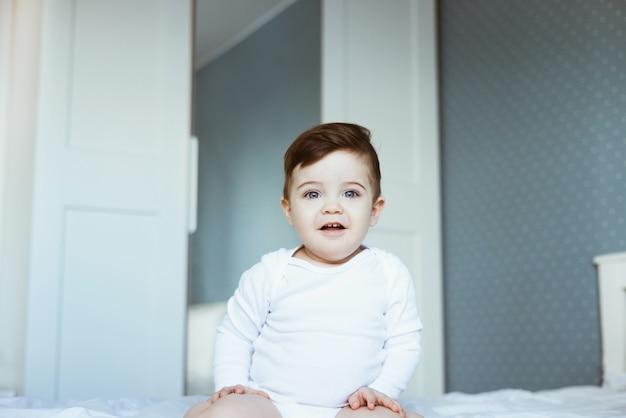 Um retrato de um lindo bebê menino em um macacão branco sentado na cama e rindo. rosto de bebê feliz, no quarto em casa, vista lateral