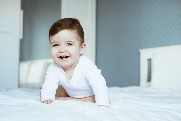 Um retrato de um lindo menino em um macacão branco sentado na cama e rindo.