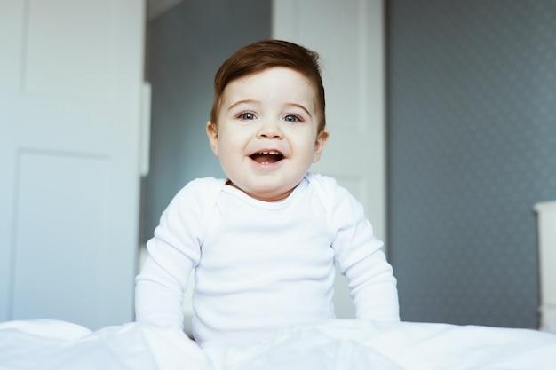 Um retrato de um lindo menino pequeno em um macacão branco sentado na cama e rindo com uma carinha feliz de bebê no quarto em casa