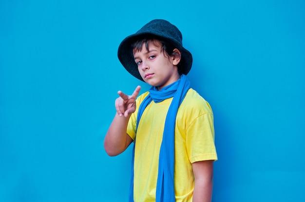 Um retrato de um menino desafiador em uma camiseta amarela
