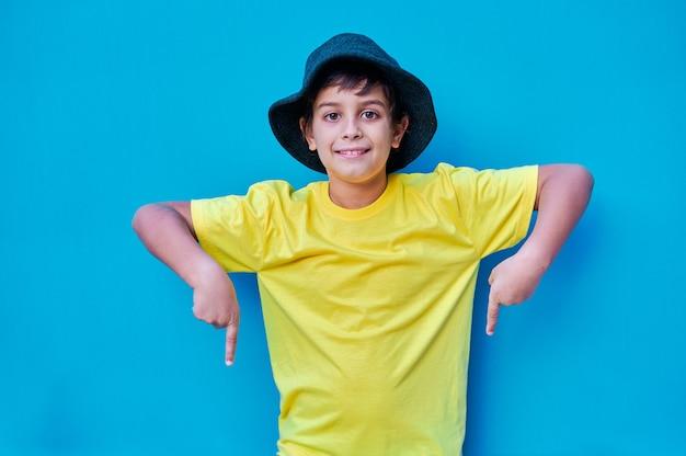 Um retrato de um menino em uma camiseta amarela aponta para baixo com os dedos indicadores