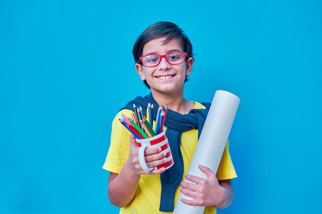 Um retrato de um menino inteligente e estudioso com óculos vermelhos em uma camiseta amarela segurando na mão um copo com muitos lápis de cor e um rolo de papel de pintura na parede azul espaço para cópia