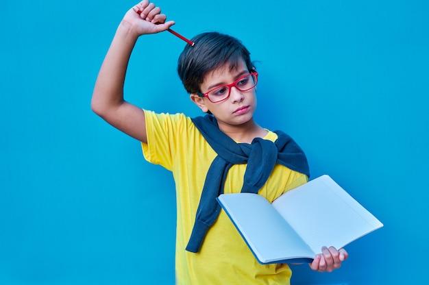 Um retrato de um menino inteligente e estudioso com óculos vermelhos