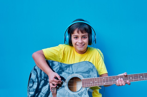 Um retrato de um menino sorridente com uma camiseta amarela e fones de ouvido azuis tocando violão