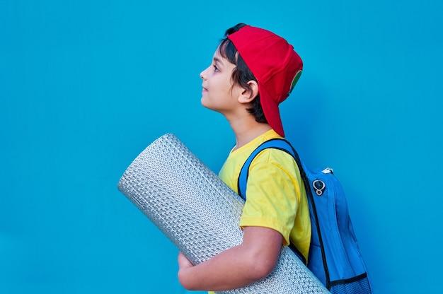 Um retrato de um menino sorridente em uma camiseta amarela e boné vermelho com um tapete e uma mochila