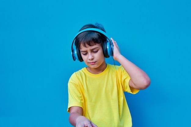 Um retrato de um menino sorridente em uma camiseta amarela e fones de ouvido azuis tocando dj