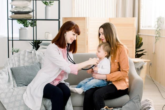 Um retrato de um pediatra feminino caucasiano, usando o estetoscópio, examinando uma menina nas mãos da mãe
