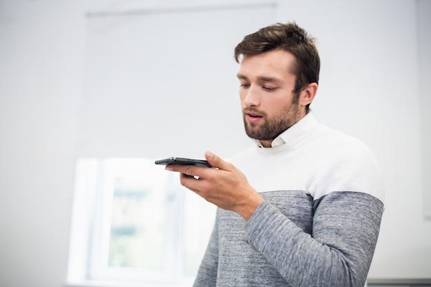 Um retrato de um trabalhador de escritório conversando com alguém usando o modo de alto-falante no telefone
