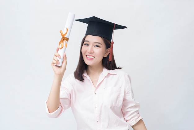 Um retrato de uma bela jovem asiática com tampa de educação sobre o espaço em branco studio, conceito de educação.