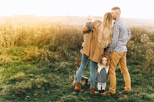 Um retrato de uma família feliz que está jogando no por do sol