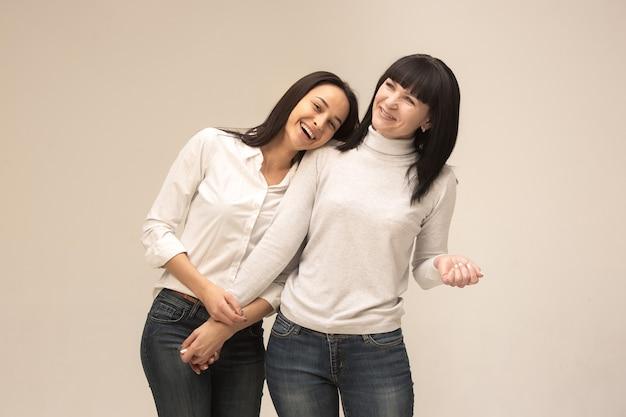 Um retrato de uma feliz mãe e filha no estúdio em fundo cinza. emoções humanas positivas e conceito de expressões faciais