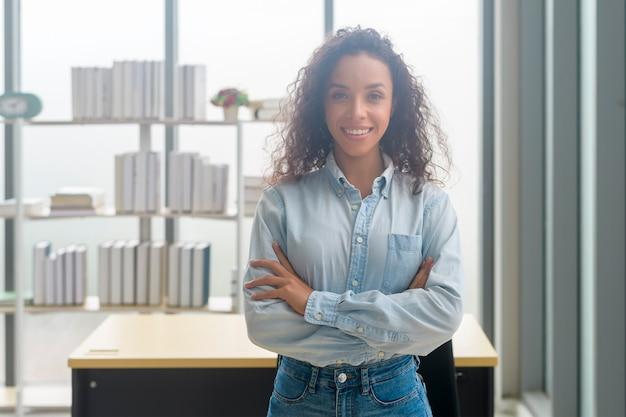 Um retrato de uma jovem empresária africana sorrindo em um escritório moderno