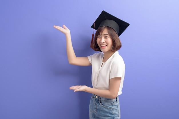 Um retrato de uma jovem estudante asiática com chapéu de formatura.
