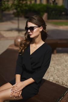 Um retrato de uma jovem modelo mulher em um vestido preto e óculos escuros, sentada no banco e desfrutando ...