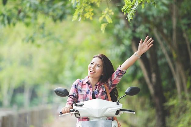Um retrato de uma jovem mulher asiática andando de moto em um parque, mão para cima
