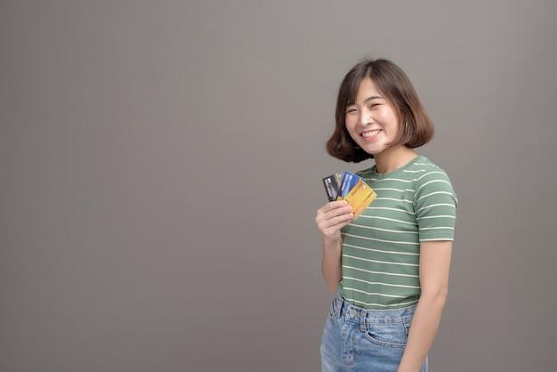Um retrato de uma jovem mulher asiática bonita segurando cartão de crédito e smartphone isolados sobre cinza