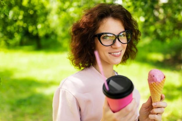 Um retrato de uma jovem mulher caucasiana de olhos verdes, sorriso perfeito, lábios carnudos, óculos caminha na natureza e bebe café ou coquetel e come um sorvete