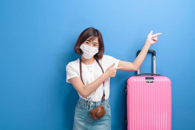 Um retrato de uma jovem viajante com máscara facial, novo conceito de viagens normais
