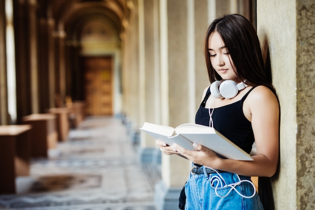 Um retrato de uma mulher asiática com livro estudante universitário no campus