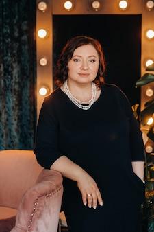 Um retrato de uma mulher de negócios em um vestido preto e com miçangas no pescoço está perto de uma cadeira no interior.