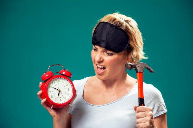Um retrato de uma mulher irritada com máscara de dormir na cabeça segurando hummer queria esmagar o despertador vermelho pela manhã.