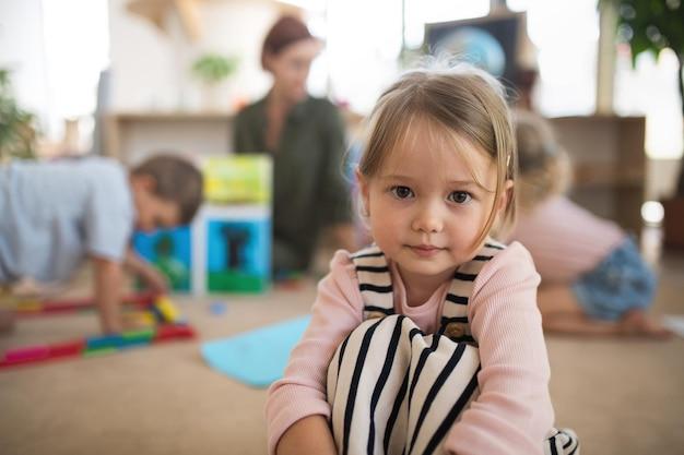 Um retrato de uma pequena menina da escola maternal dentro de casa na sala de aula, olhando para a câmera.
