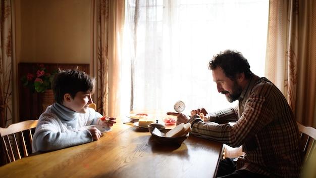 Um retrato de uma pobre menina com o pai comendo dentro de casa em casa, o conceito de pobreza.