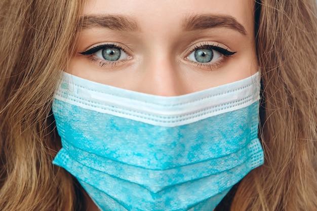 Um retrato do close-up de uma mulher em uma máscara médica. uma mulher assustada. a mulher tem medo de contrair coronavírus. covid-2019. uma pandemia global.