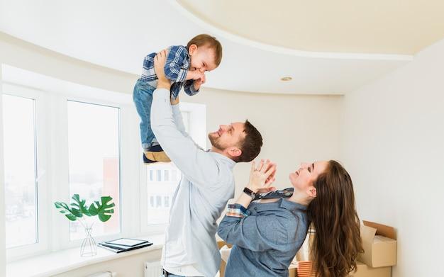 Um retrato do jovem casal brincando com um bebê em uma nova casa