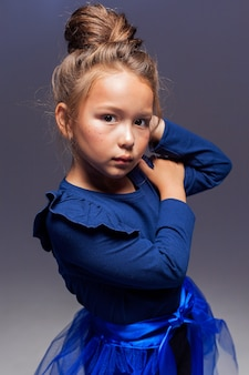 Um retrato elegante de uma menina modelo posando profissionalmente em um fundo escuro. uma garota com legging preta, uma jaqueta azul e uma cauda azul. o conceito de moda infantil.