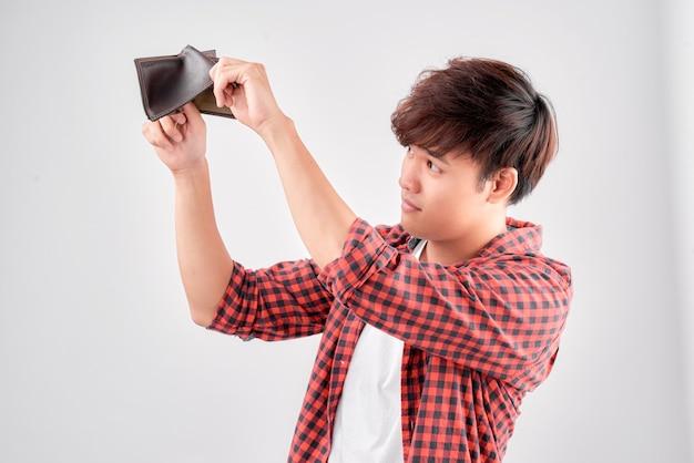 Um retrato em close de um homem asiático, chocado e surpreso, sem palavras, segurando uma carteira vazia