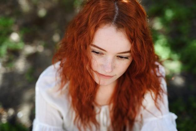 Um retrato em close-up de uma jovem triste ao ar livre na cidade.