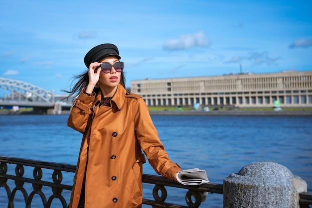 Um retrato feminino de aparência europeia no aterro em um dia ensolarado de primavera com um jornal em ...