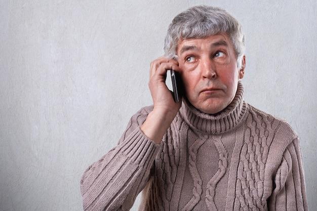 Um retrato horizontal de homem maduro, com cabelos grisalhos e rugas, vestido de camisola quente, segurando o telefone móvel