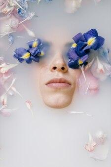 Um retrato sensual de uma mulher em um banho de leite e flores tratamentos de spa para pele macia