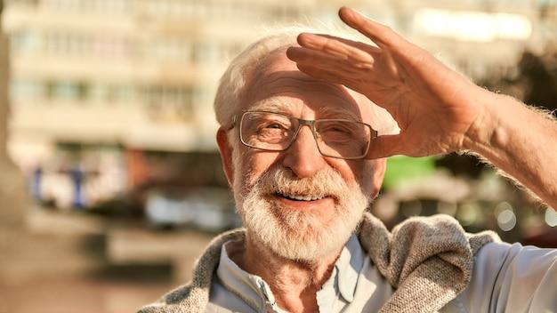 Um retrato tão bom de dia de homem barbudo sênior feliz e bonito de óculos, olhando para a câmera e