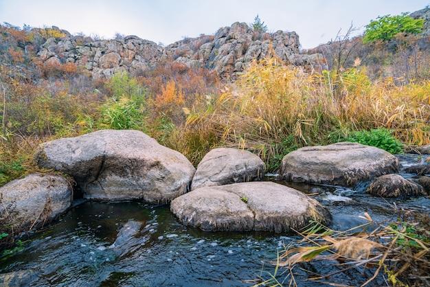 Um riacho rápido, raso e limpo corre entre pedras grandes e lisas