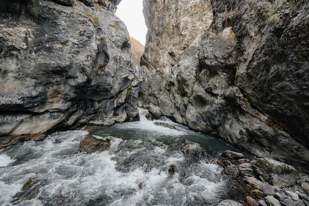 Um rio de montanha tempestuosa flui através de um desfiladeiro de montanhas. natureza.