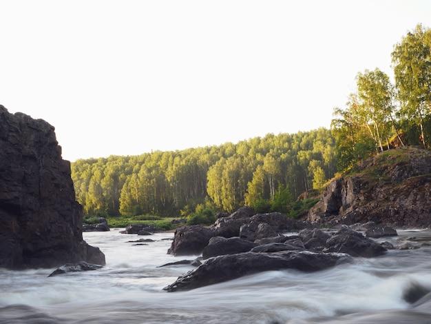 Um rio tempestuoso entre rochas e florestas, uma bela paisagem. rio de montanha com corredeiras. fundo natural ou tela inicial.
