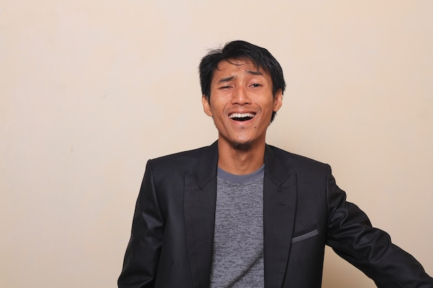 Um riso bonito jovem asiático, feliz e alegre, vestindo um terno com uma camisola dentro
