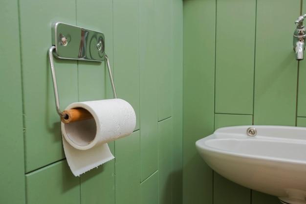 Um rolo branco de papel higiênico macio pendurado ordenadamente em um suporte cromado moderno na parede verde de um banheiro. design moderno