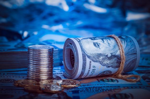 Um rolo de dólares com moedas no fundo de notas de cem dólares espalhados
