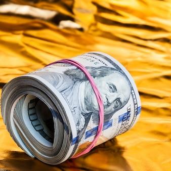 Um rolo de dólares encontra-se em um fundo de ouro.