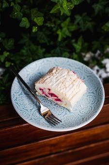 Um rolo de merengue com framboesas num prato azul com um garfo