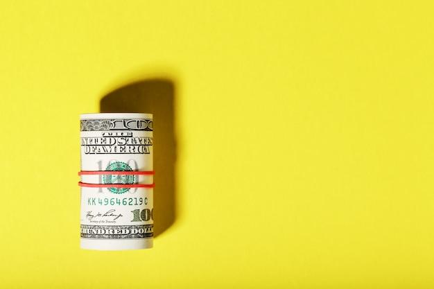 Um rolo de notas americanas de cem dólares é amarrado com um elástico vermelho sobre um fundo amarelo.