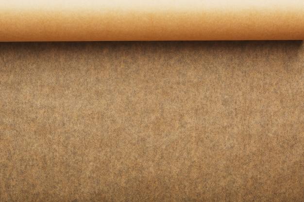 Um rolo de papel de pergaminho marrom desdobrado, para assar o alimento dentro em um fundo escuro, vista superior.