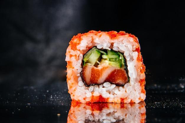 Um rolo de sushi em um fundo preto é refletido na mesa de espelho