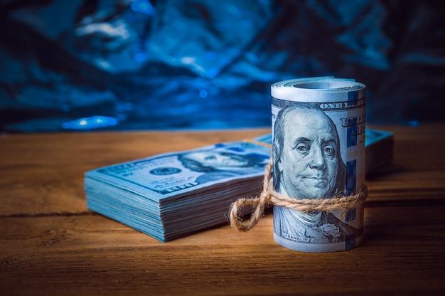 Um rolo dos dólares com um bloco dos dólares no fundo de placas de madeira textured na luz azul.